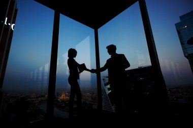 Silhouettes of businesspeople shaking hands
