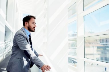 Intelligent man looking in office window