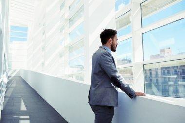 Intelligent man looking in office window