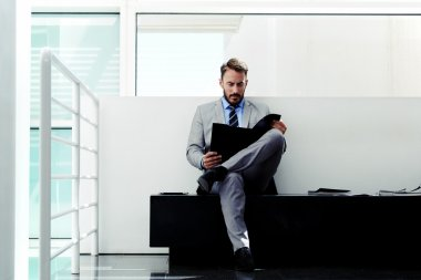 Confident man reading paper documents