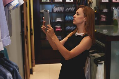Businesswoman with touch pad in her boutique