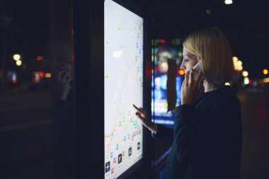 Woman touching digital display on bus stop