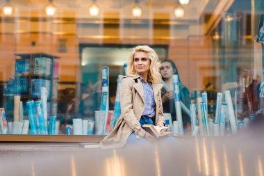 Stylish woman sitting on a shop sill