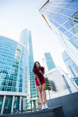 Woman posing near modern office building