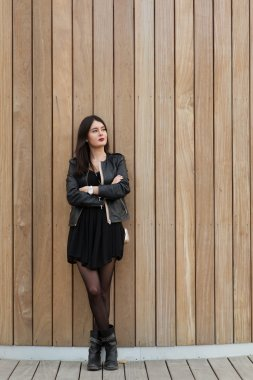Half length portrait of a fashionable woman thinking about something while standing on copy space background, young beautiful dreamy female with good look posing for the camera against wooden wall stock vector