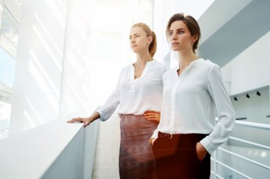 Half length portrait of a two female managing directors resting in hallway after successful presentation, young businesswomen concentrated looking in window while standing in modern office interior