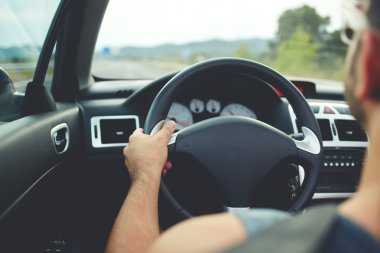 male driver sitting at steering wheel