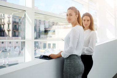 businesswomen posing near office window indoors