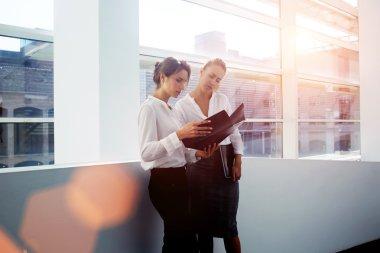 businesswomen considering paper documents