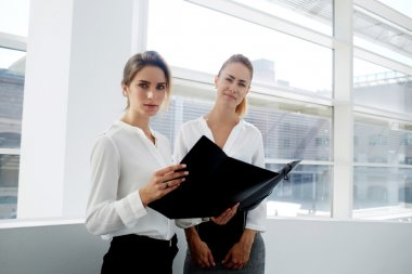 businesswomen considering paper documents