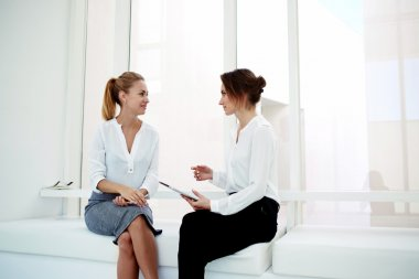 two women sitting in modern office