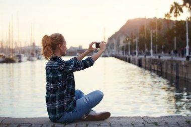 Hipster girl photographing herself