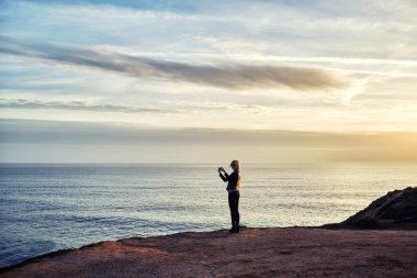 female taking photo of sea landscape