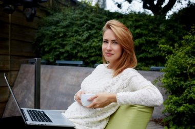 Young attractive woman looking at camera while sitting with laptop computer and cup of coffee in cozy restaurant outdoors, gorgeous female rest after video conversation via net-book posing to camera stock vector