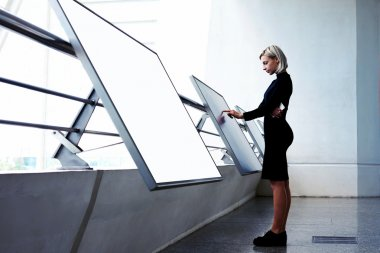Young businesswoman using interactive display