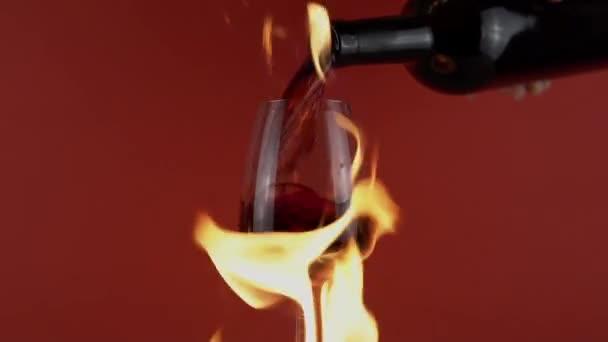 Pálení sklenice, nalévání červeného vína z láhve na sklo v ohni na pozadí
