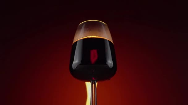 Red wine in glass on color background with fire, alcohol