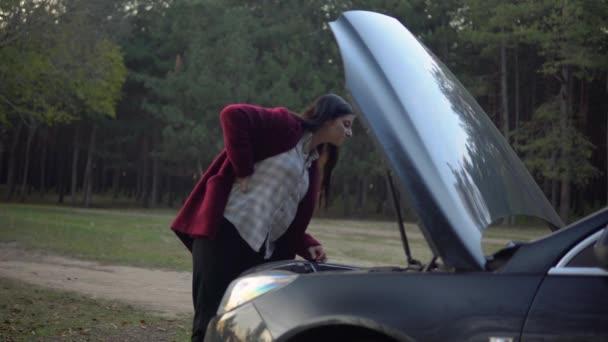 Woman near broken car, looking at motor open hood, breakdown car on forest road