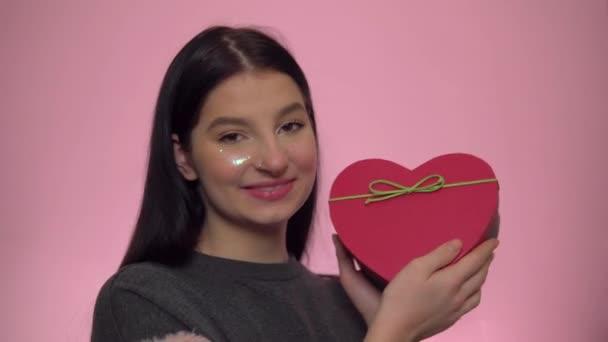 Glückliche Frau bekommt Geschenk zum Valentinstag, herzförmige Geschenkbox