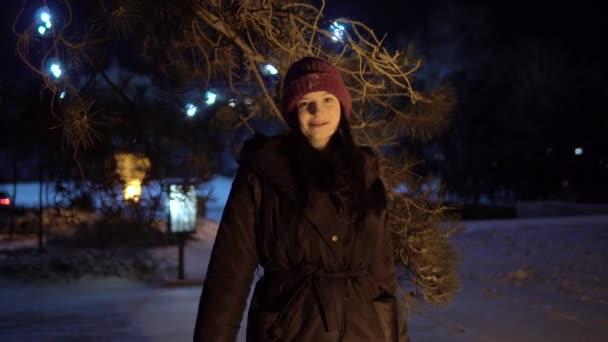 Šťastná žena nadšená zimou zasněžené počasí v noci chůze.