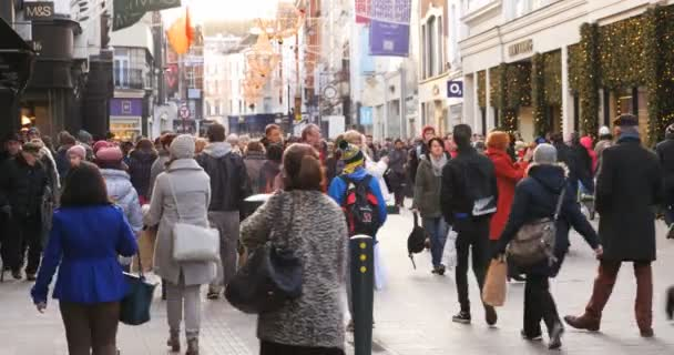 Crowd of anonymous people walking on busy Dublin street