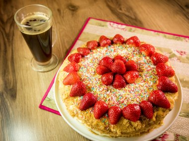 honey cake with strawberry on top and coffee table