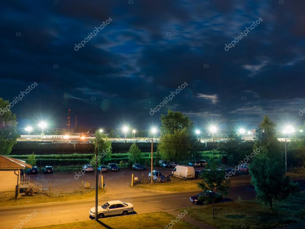 car parking at night with street lights and dark clouds
