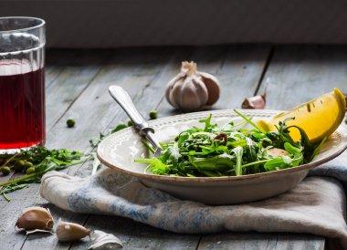 green salad with arugula, cheese, almonds, lemon, garlic