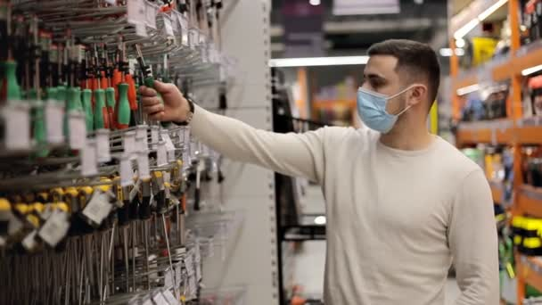 Young man wearing disposable medical mask chooses a screwdriver in the tool shop