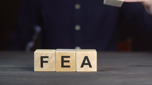 A man in a shirt composes the word FEAR from wooden cubes, close up