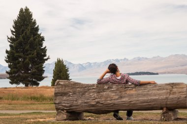 woman sitting on a wooden bench beside a lake