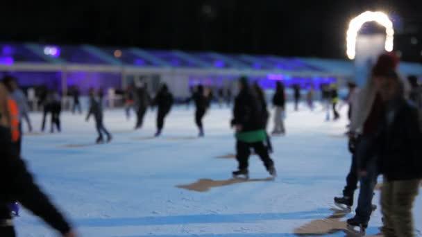 People ice skating at night