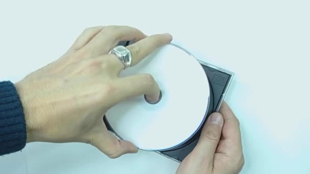 Close up footage wtih hand picks up and installs a white CD DVD disc in a black plastic box. Shot. isolated on white bakground.