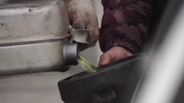 Nahaufnahme beim Betanken eines Autos aus einem Metallkanister. Verfilmung. Benzin aus den Händen eines Mannes mit Handschuhen in ein Auto oder einen Mechanismus auf der Straße gießen