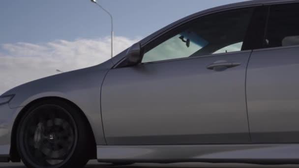 Boční pohled na moderní silné jízdy autem na letní dálnici. Záběry. Perfektní auto jede rychle na venkovské silnici.