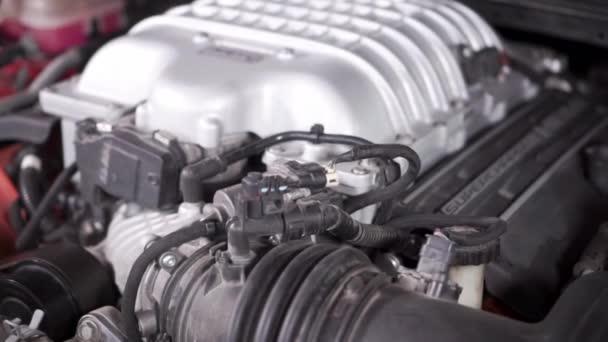 Indítom a motort egy sportkocsiban. Felvétel. A csatlakozók és görgőik meghajtó övei forogni kezdenek, a motor rezgése a csillapító tartályokba kerül.