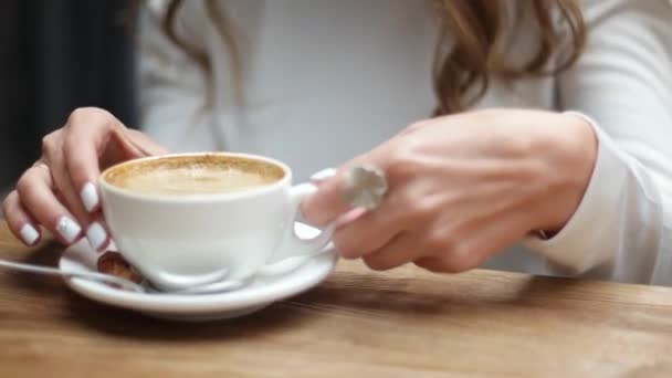 Side view of women hands with white cup of black coffe on light wooden table background. Media. Closeup shot of delicate girls hands taking small cup of coffee.