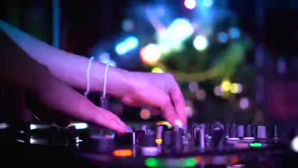 Detailní záběr ženské ruční práce s DJ mixer panel v nočním klubu. Záběry. Ruce mistra dotýkání jezdců a tlačítek hraje elektronickou hudbu. Koncept nočního života, relaxace a příjemné chvíle.