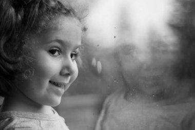 Küçük kız evinin penceresinden dışarı bakıyor. Seçici Odaklanma Kızı.