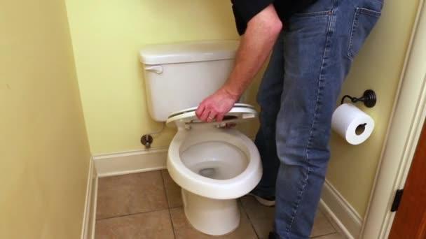 Hauseigentümer installiert neuen Toilettensitz