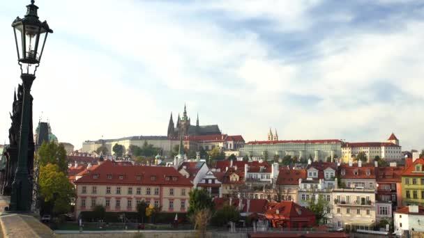 pouliční osvětlení na Karlově mostě ze 14. století a Pražský hrad a katedrála sv. Víta v pozadí a tekoucí řeka Vltava při západu slunce ve večerních hodinách v centru starého města