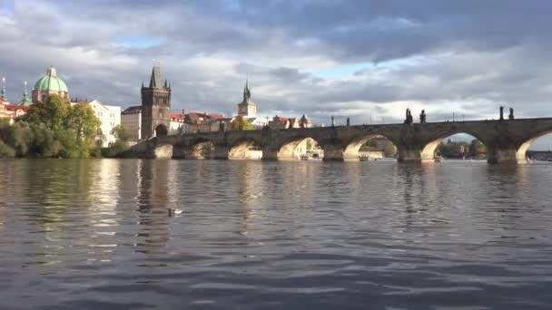 pohled na Karlův most z roku 1402 a tekoucí Vltavu a mosty a provoz na nich v centru Prahy při západu slunce v České republice
