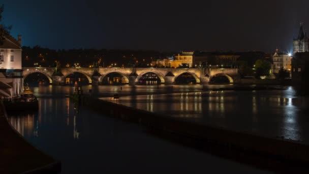 osvětlil Karlův most z roku 1402 v centru Prahy na tekoucí řece Vltavě v noci. na povrchu se odrážejí světla. Pilíře kamenného mostu v Praze.