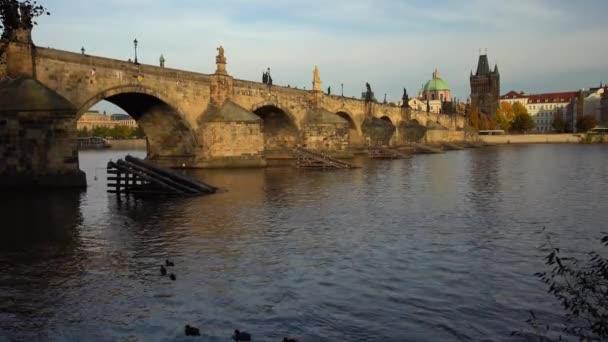 starý kamenný Karlův most ze 14. století na hladině Vltavy ozářený sluncem při západu slunce v centru Prahy a mraky na obloze