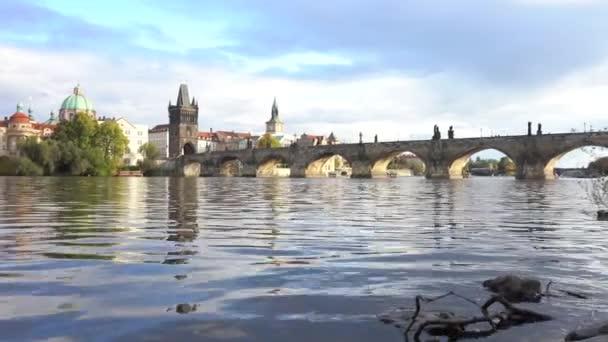 starý kamenný Karlův most ze 14. století na hladině Vltavy, ozářený sluncem při západu slunce v centru Prahy a mraky na obloze. tekoucí Vltava v centru hlavního města Prahy