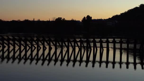 ochranné pilíře ve vodě při západu slunce na tekoucí řece Vltavě v centru Prahy