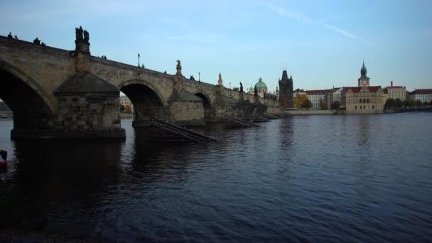 pohled na starý kamenný most ze 14. století v centru Prahy na tekoucí řece Vltavě jsou sochy a obloha je při západu slunce v České republice modrá