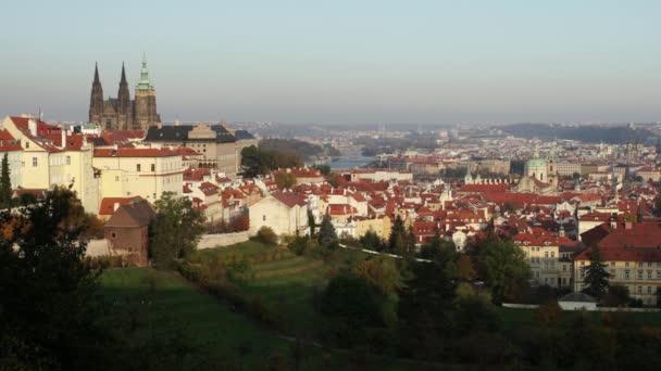 panorama katedrály sv. Víta a Pražského hradu a okolí se stromy a trávou na podzim při západu slunce a obloha je modrá v centru Prahy