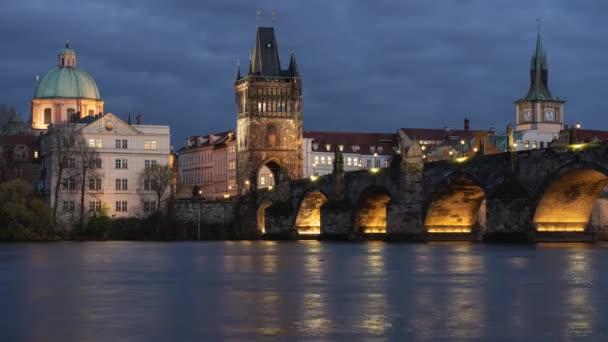 časový odstup řeky Vltavy a kamenného starého Karlova mostu ze 14. století a světlo pouličního osvětlení v noci v centru Prahy v České republice