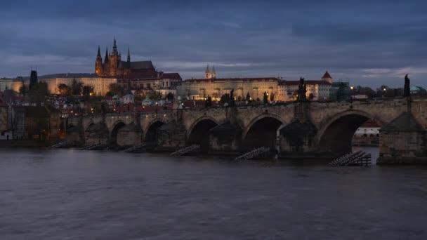 statický záběr Pražského hradu a katedrály sv. Víta a Karlova mostu na tekoucí řece Vltavě v centru starého města Prahy při západu slunce a raccích letících v